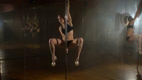 Jonge vrouwelijke pooldanser die gymnastiek- spleten in dansstudio doen stock footage