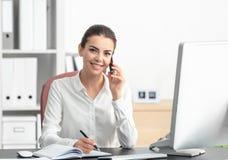 Jonge vrouwelijke receptionnist die op telefoon spreken royalty-vrije stock foto's