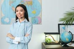 Jonge vrouwelijke reisbureauadviseur in reisagentschap die hoofdtelefoon dragen royalty-vrije stock fotografie