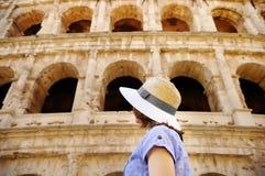 Jonge vrouwelijke reiziger die op beroemd kijken Colosseum in Rome royalty-vrije stock fotografie