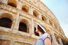 Jonge vrouwelijke reiziger die op beroemd kijken Colosseum in Rome stock foto's