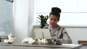 Jonge vrouwelijke schrijver die aan schrijfmachine in witte ruimte werken stock footage