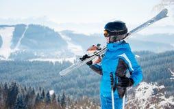 Jonge vrouwelijke skiër die met het ski?en materiaal bij de toevlucht van de de winterski in mooie zonnige dag genieten van stock fotografie