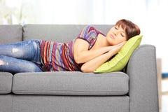 Jonge vrouwelijke slaap op bank thuis royalty-vrije stock foto's