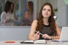 Jonge vrouwelijke Stagiair die aan Laptop in Bureaubinnenland werken royalty-vrije stock fotografie