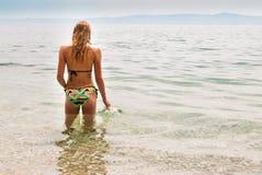 Jonge vrouwelijke status in het overzees wat betreft de oppervlakte, linkermening Royalty-vrije Stock Foto