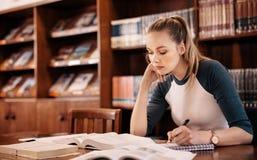 Jonge vrouwelijke student in bibliotheek royalty-vrije stock foto's