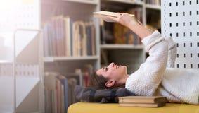 Jonge vrouwelijke student die in de bibliotheek bestuderen Stock Afbeelding