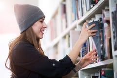Jonge vrouwelijke student die in de bibliotheek bestuderen Stock Fotografie