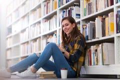 Jonge vrouwelijke student die in de bibliotheek bestuderen Stock Foto's