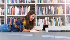 Jonge vrouwelijke student die in de bibliotheek bestuderen Stock Foto