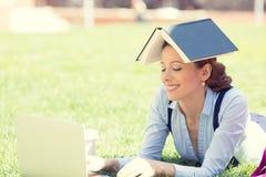 Jonge vrouwelijke student die openlucht laptop met behulp van Stock Afbeelding