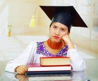 Jonge vrouwelijke student die traditionele blouse en graduatiehoed dragen, die door bureau met boeken zitten in geërgerde voorzij Stock Afbeelding
