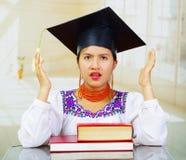 Jonge vrouwelijke student die traditionele blouse en graduatiehoed dragen, die door bureau met boeken zitten vooraan worden gesta Stock Foto's