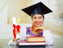 Jonge vrouwelijke student die traditionele blouse en graduatiehoed dragen, die door bureau met boeken zitten in voorzijde, het gl Royalty-vrije Stock Foto's