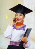 Jonge vrouwelijke student die traditionele blouse en graduatiehoed dragen, die zwart diplomaboekje houden terwijl het spreken Stock Fotografie