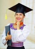 Jonge vrouwelijke student die traditionele blouse en graduatiehoed dragen, die zwart diplomaboekje houden terwijl wat betreft kin Royalty-vrije Stock Fotografie