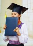 Jonge vrouwelijke student die traditionele blouse en graduatiehoed dragen, houdend zwart diplomaboekje, die het kussen met ogen Royalty-vrije Stock Foto