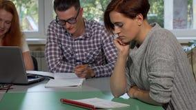 Jonge vrouwelijke student die vermoeid en verward terwijl het schrijven in haar handboek kijken stock footage