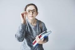 Jonge vrouwelijke student die zorgvuldig en boeken houden kijken royalty-vrije stock foto
