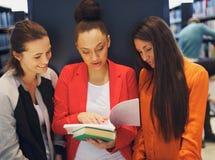 Jonge vrouwelijke studenten die een boek in bibliotheek delen Stock Foto's