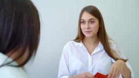 Jonge vrouwelijke studenten die kleurenkaarten nemen en taak in middelbare schoolklaslokaal bespreken stock footage