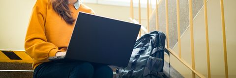 Jonge vrouwelijke studentzitting op treden op school, het schrijven poging op haar laptop Het concept van het onderwijs stock afbeelding