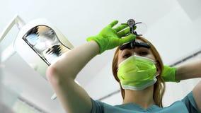 Jonge vrouwelijke tandarts die in vergrootglazen voor behandelingsprocedure voorbereidingen treffen stock foto's