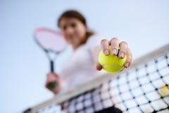 Jonge vrouwelijke tennisspeler met tennisbal en racket die voorbereidingen treffen te dienen royalty-vrije stock afbeeldingen