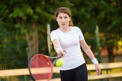 Jonge vrouwelijke tennisspeler met tennisbal en racket die voorbereidingen treffen te dienen stock afbeeldingen