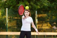 Jonge vrouwelijke tennisspeler met tennisbal en racket die voorbereidingen treffen te dienen stock fotografie