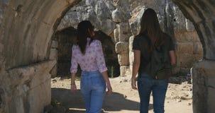 Jonge vrouwelijke toeristen die in Oude stad Perge, openlucht antiek historisch museum lopen