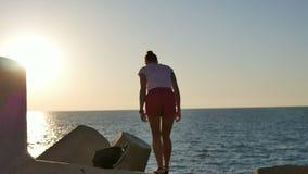Jonge vrouwelijke toeristenzitting neer op de rotsen om het overzees te bekijken stock video