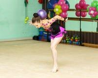 Jonge vrouwelijke turner die geslepen truc met bal doen Royalty-vrije Stock Afbeelding
