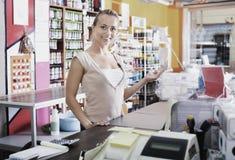 Jonge vrouwelijke verkoper die zich bij loonsbureau bevinden in supermarkt royalty-vrije stock afbeelding
