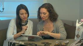 Jonge vrouwelijke verkoper en aantrekkelijke vrouwen uitgezochte juwelen die tabletzitting op comfortabele bank in een juwelenops stock footage