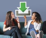 Jonge vrouwelijke vrienden die een downloadpictogram houden stock afbeeldingen