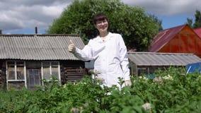 Jonge vrouwelijke wetenschapper die duim tonen tegen een achtergrond van aardappelgebied stock footage