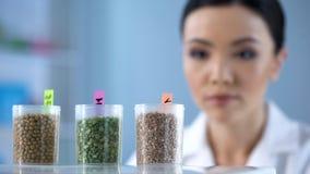Jonge vrouwelijke wetenschapper die flessen met zaden, voedingseigenschappen onderzoeken royalty-vrije stock foto