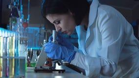 Jonge vrouwelijke wetenschapper die onderaan een microscoop kijken stock videobeelden