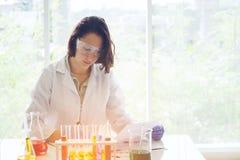 Jonge vrouwelijke wetenschapper in laboratoriumarbeider die medisch onderzoek binnen maken royalty-vrije stock foto