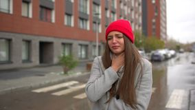 Jonge vrouwelijke zieke vrouw, meisje met keelpijnpijn en smerige hoest, die bij straat buiten hoesten, gezondheidszorg, griep, m stock footage