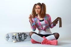 Jonge vrouwelijke zitting en holding een tablet Stock Foto's