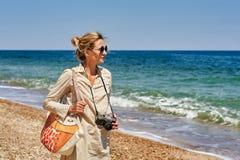 Jonge vrouwen Amateurfotograaf op een gang door het overzees met een oude camera royalty-vrije stock foto