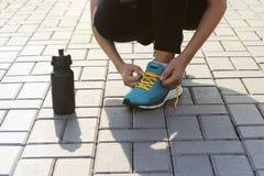 Jonge vrouwen bindende schoenveters op tennisschoenen op betonmolens Status naast een fles water Oefening in openlucht Royalty-vrije Stock Afbeelding