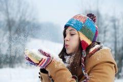 Jonge vrouwen blazende sneeuw aan weg Stock Foto's
