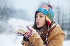 Jonge vrouwen blazende sneeuw aan weg Royalty-vrije Stock Afbeelding