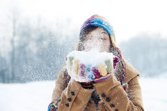 Jonge vrouwen blazende sneeuw aan weg Royalty-vrije Stock Fotografie
