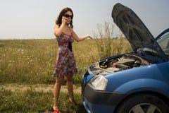 Jonge vrouwen dichtbij gebroken auto royalty-vrije stock afbeeldingen