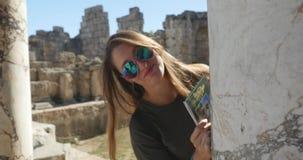 Jonge vrouwen die achter antieke kolom in Oude stad Perge, openlucht antiek historisch museum hidding